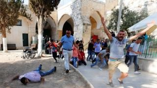 Palestinians return to holy site after Israel security reversal